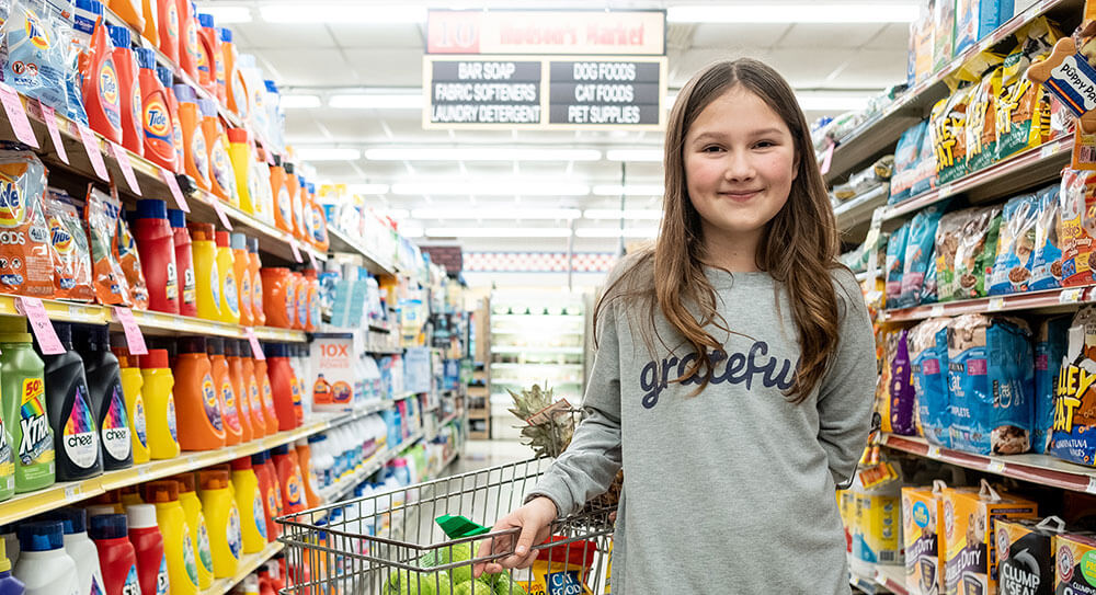 Girl standing in a store aisle with grocery cart