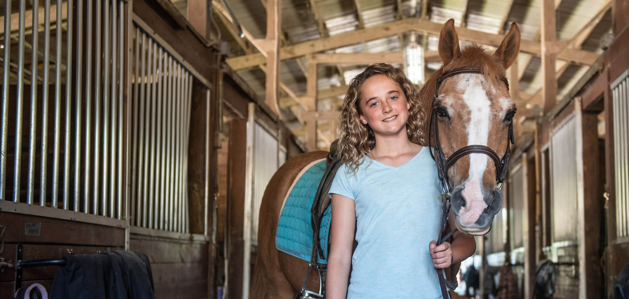 Young girl holding the reigns of a horse