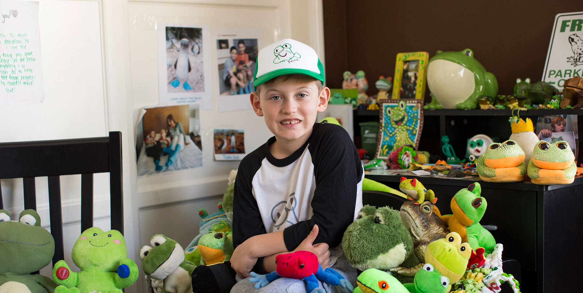 Image of a little boy sitting with stuffed animal frogs