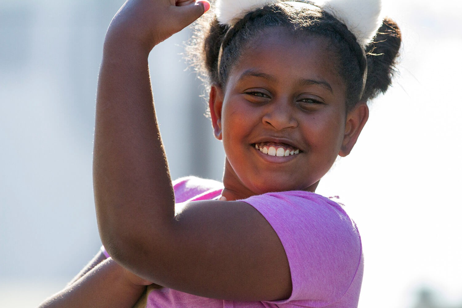 young girl wearing cat ears and holding up her arm to flex the muscle