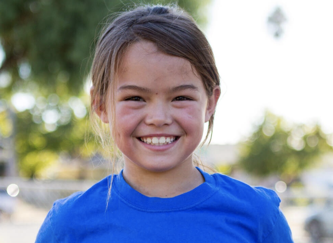 young girl in blue shirt smiling