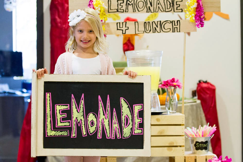young girl holding a fundraising lemonade stand