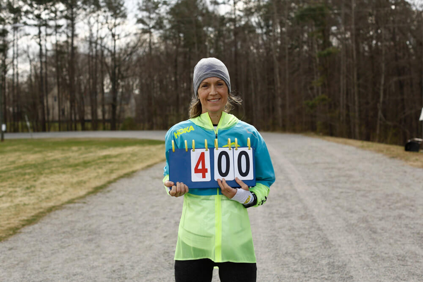 woman in running gear holding a counter sign