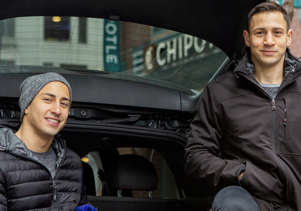two men smiling in the back of a car
