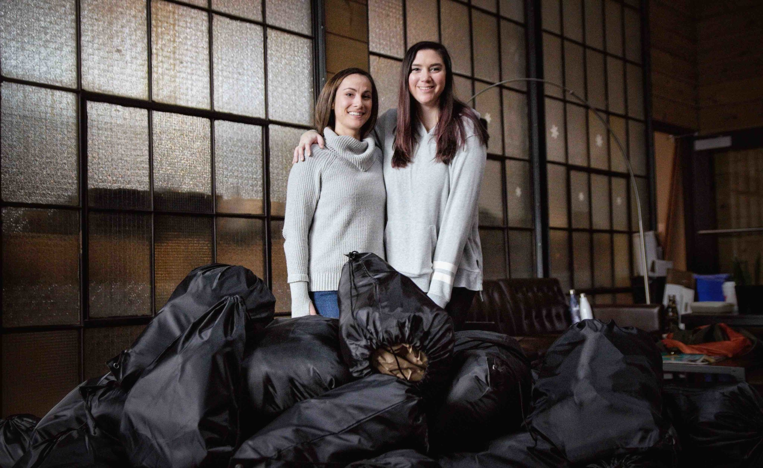 two women smiling with a pile of black drawstring bags