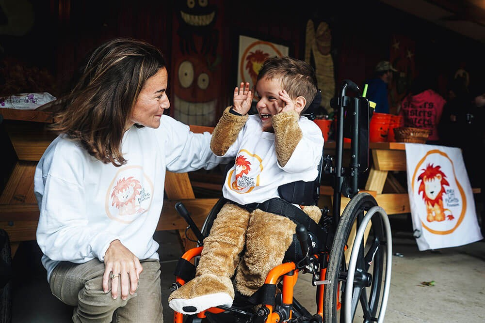 women interacting with young child in wheelchair