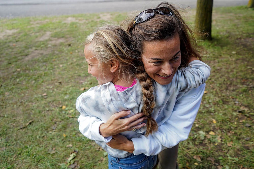 a young girl hugging her mom