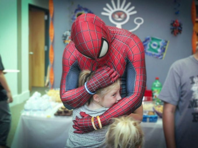 man in spiderman costume hugging young girl