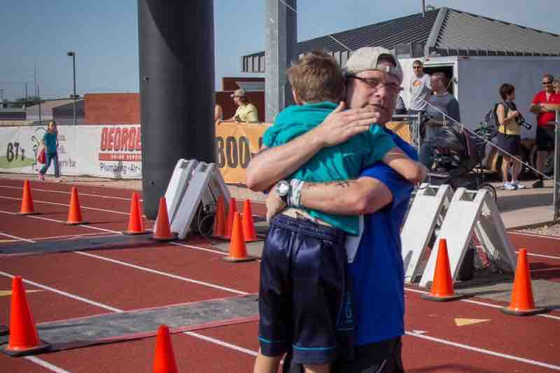 man hugging young boy on a track