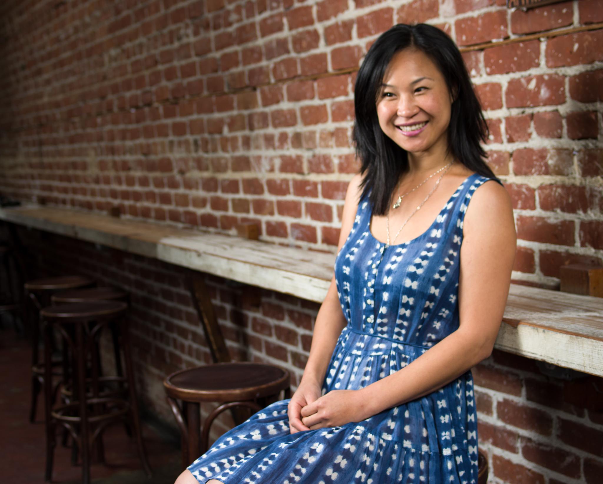woman in blue dress smiling in front of brick wall