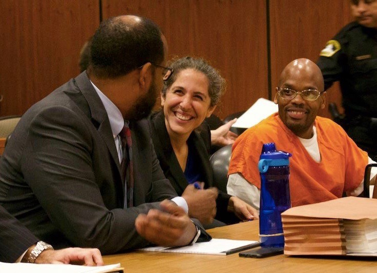 defendant and woman smiling at attorney in courtroom