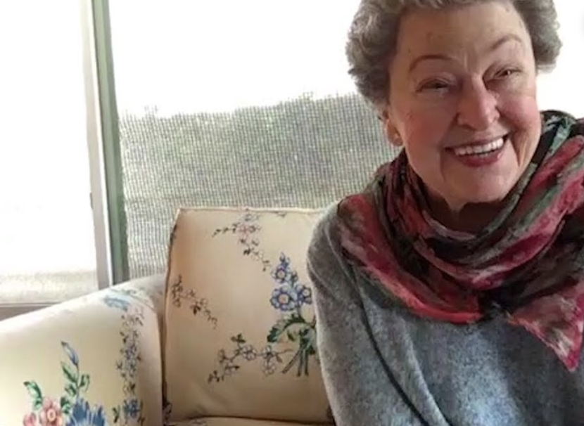 older woman in pink scarf smiling