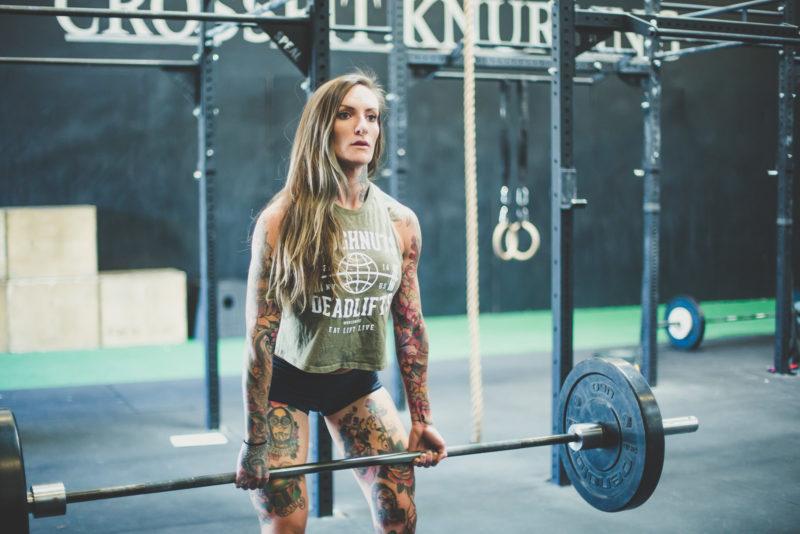 tattooed woman lifting weight