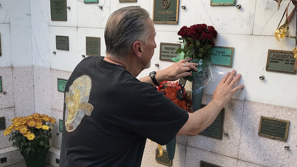 man touching gravestone and holding red roses