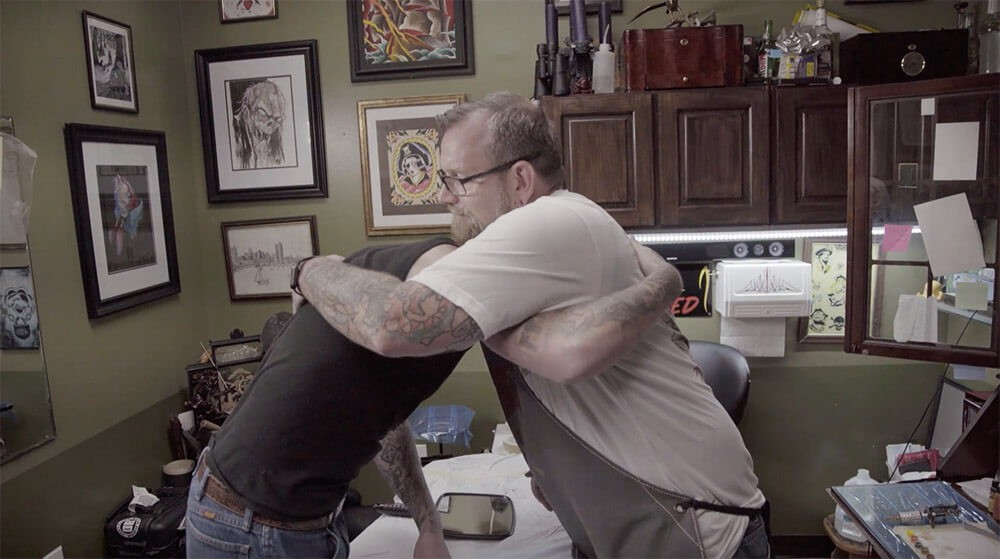 two people hugging in tattoo parlor