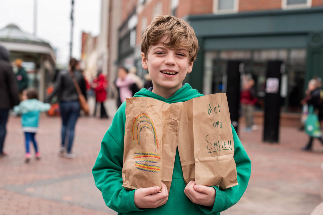boy holding two brown paper lunch bags and smiling