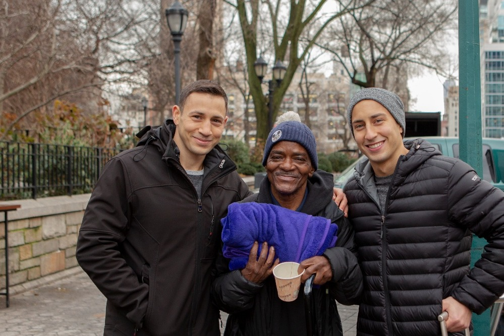 two men gifting blanket to homeless individual