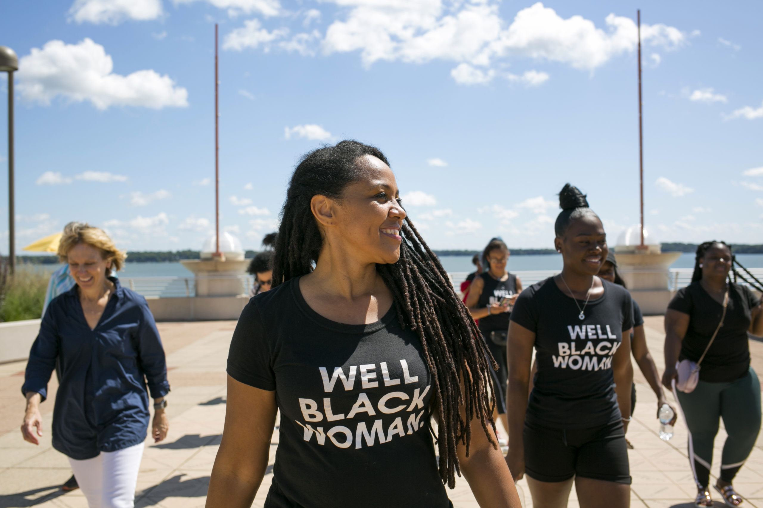 black women smiling and standing by the water