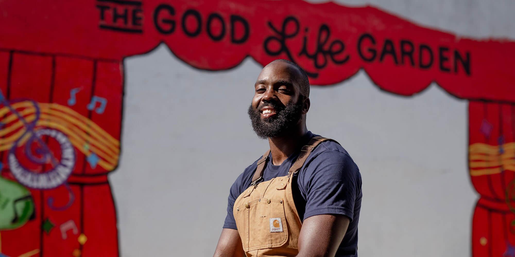 male gardener smiling in front of the good life garden sign