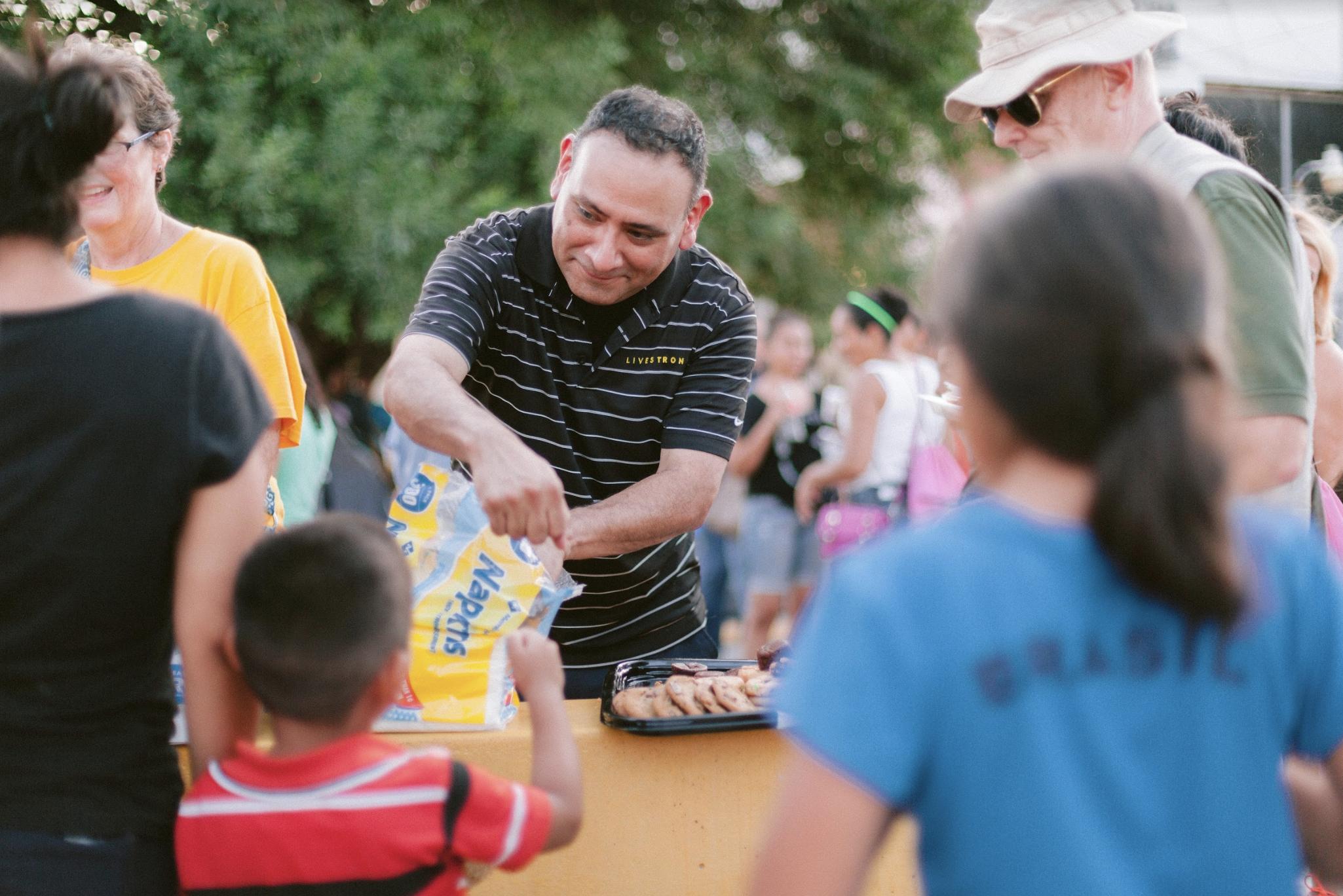 man distributing napkins for community picnic