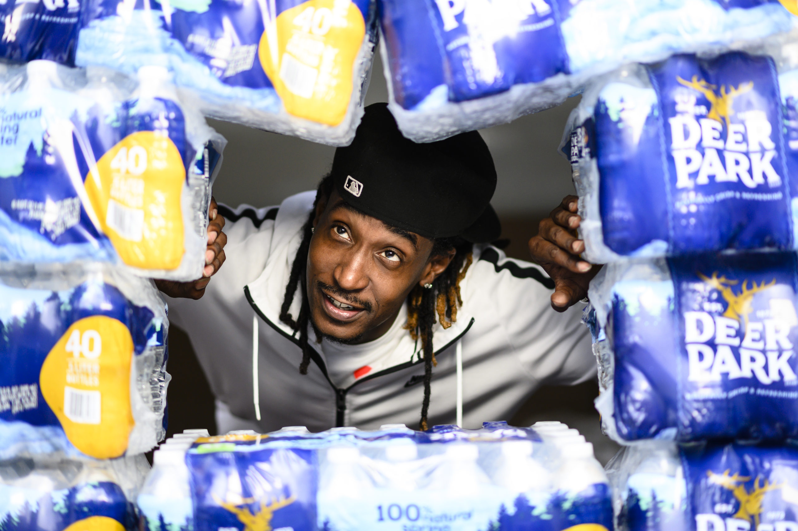 man looking out from hole made of stacked bottled water cases