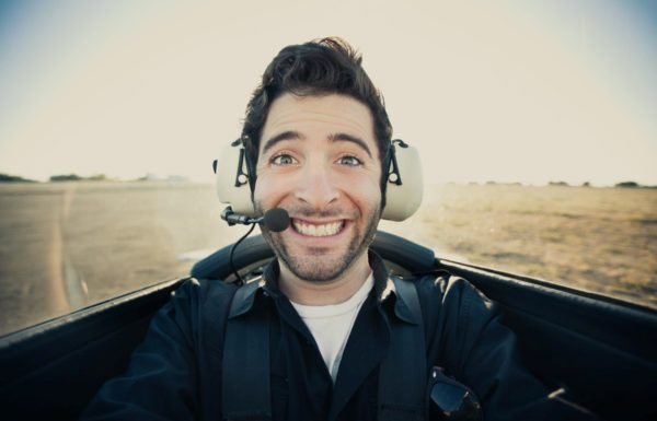man with headset smiling inside airplane cockpit