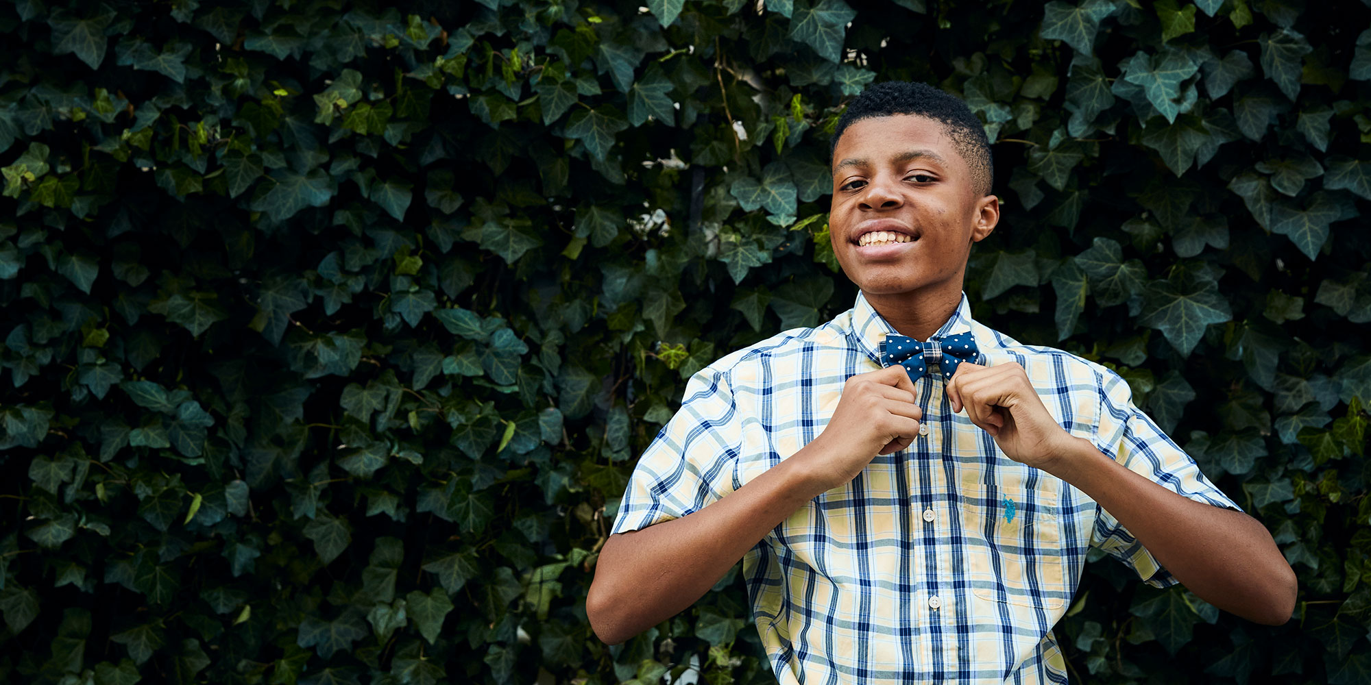young man proudly showing off a blue polkadot bowtie