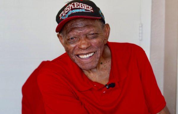 man smiling in tuskegee airmen hat