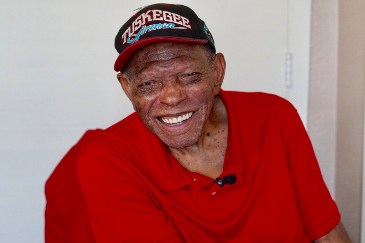 man smiling in tuskegee airmen hat