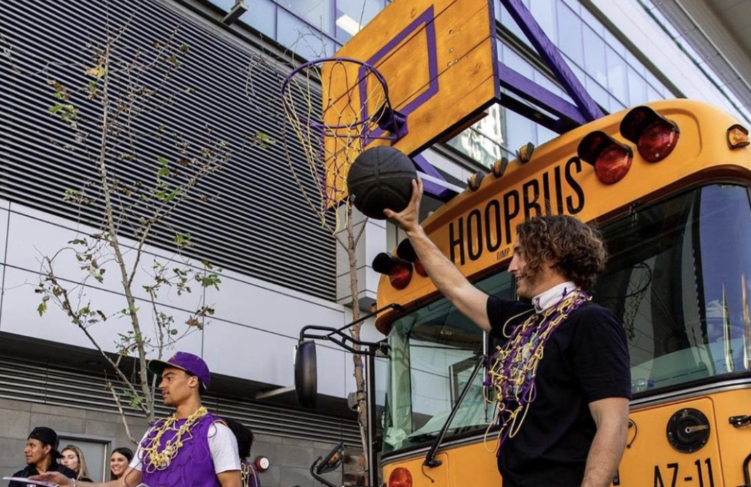 two men in LA lakers gear standing in front of basketball hoop