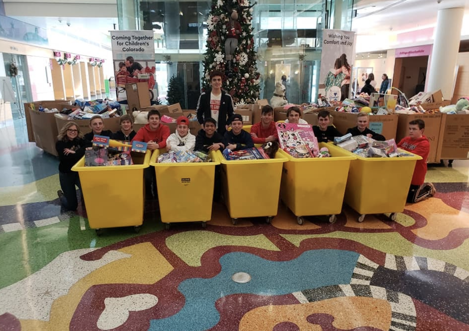 teenagers sitting in front of christmas toy donation carts