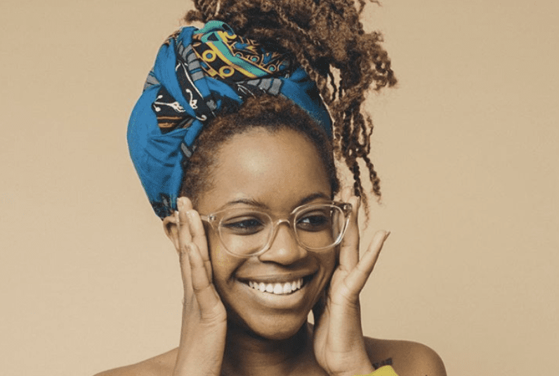 young woman with clear glasses smiling