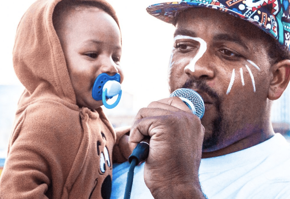A person wearing a hat and face paint holding a microphone and carrying a baby with a pacifier
