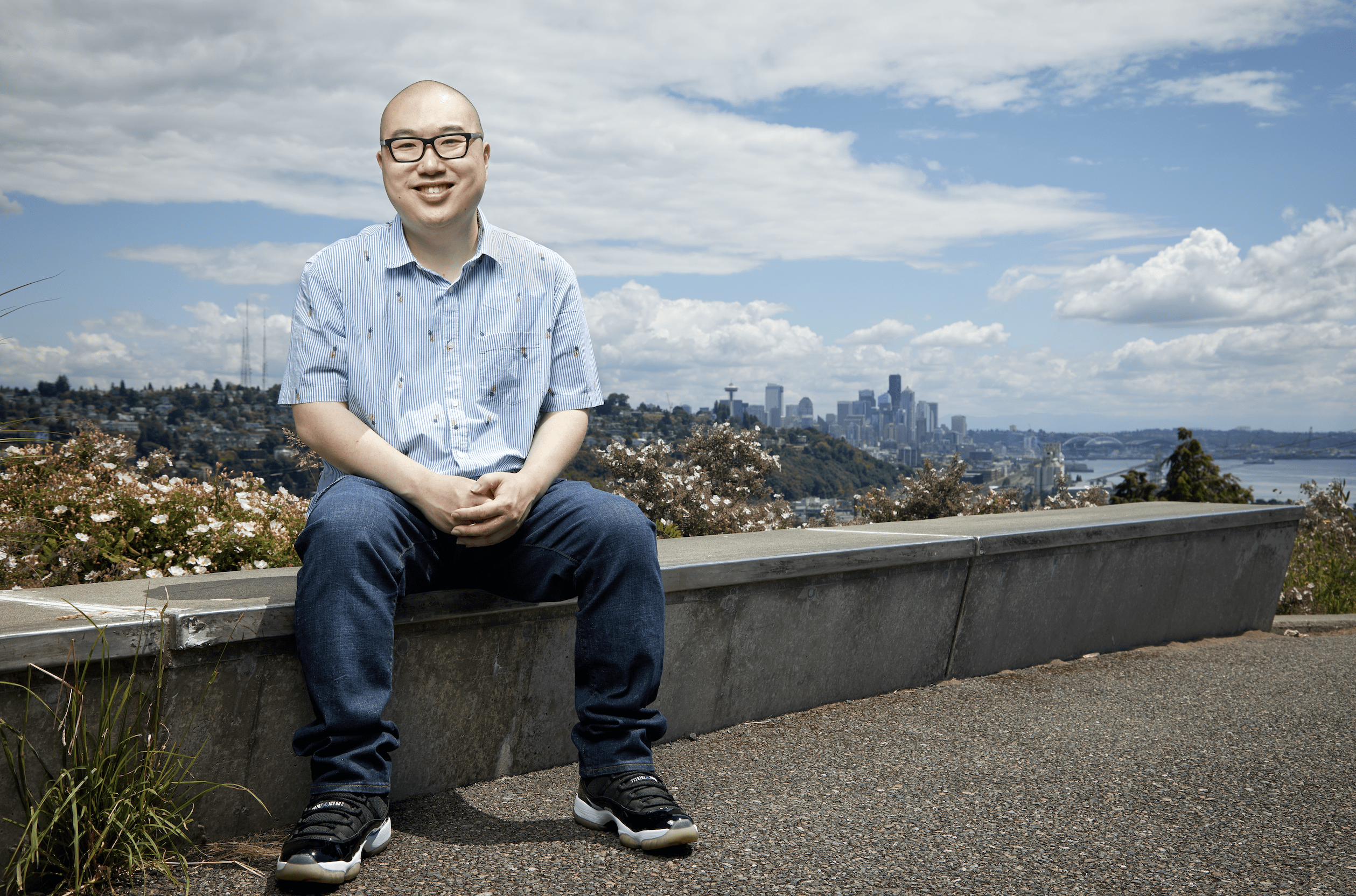 A man wearing glasses sitting on a ledge with a view of the city behind him