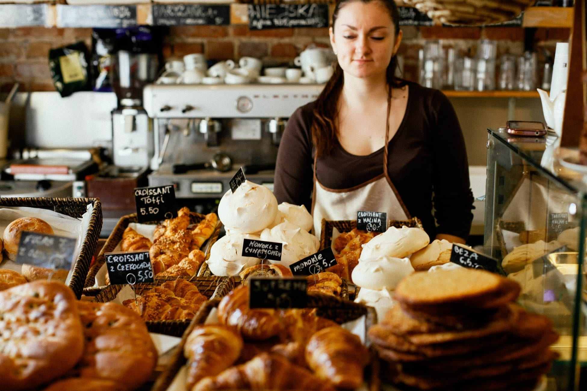 A woman standing behind a bakery counter