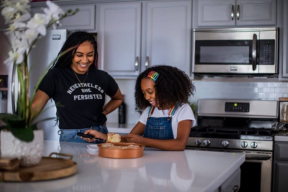 A woman and her young daughter baking in the kitchen