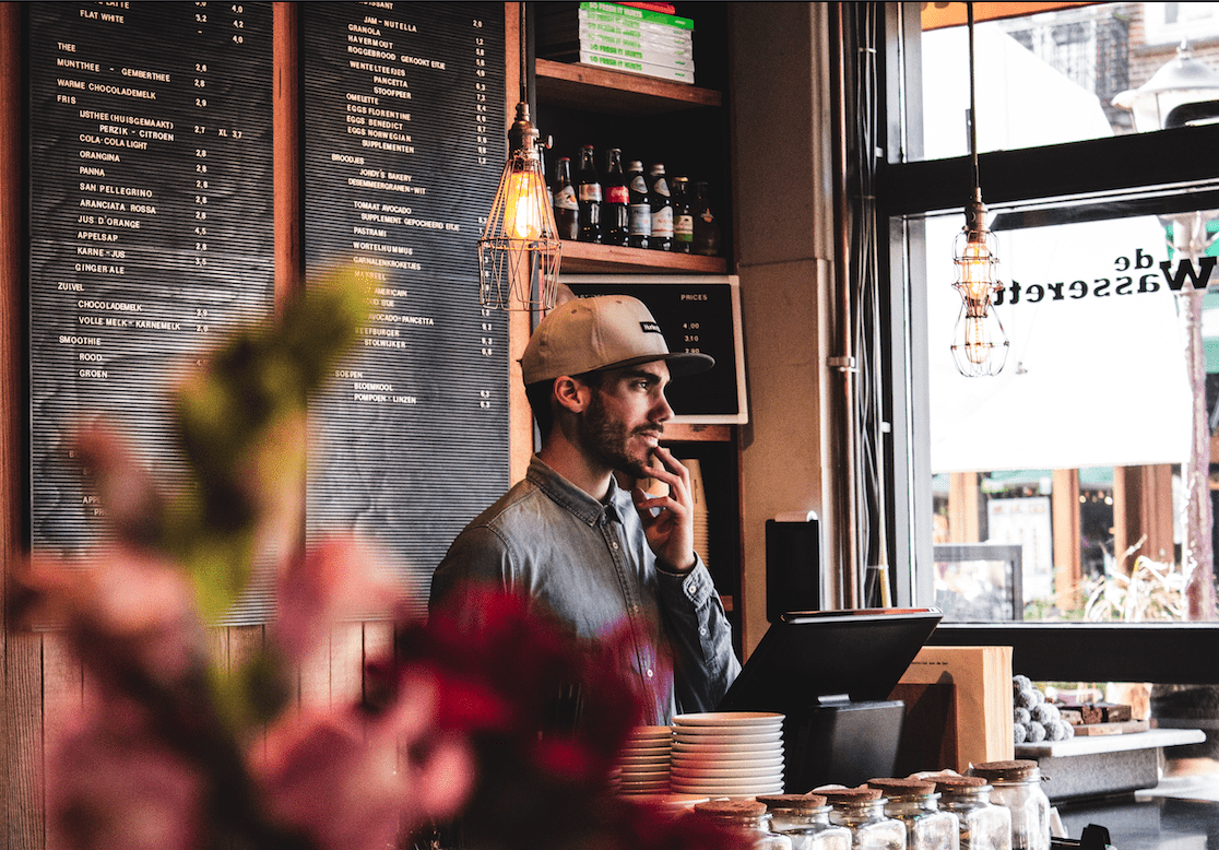 restaurant worker wearing a gray shirt standing behind a counter