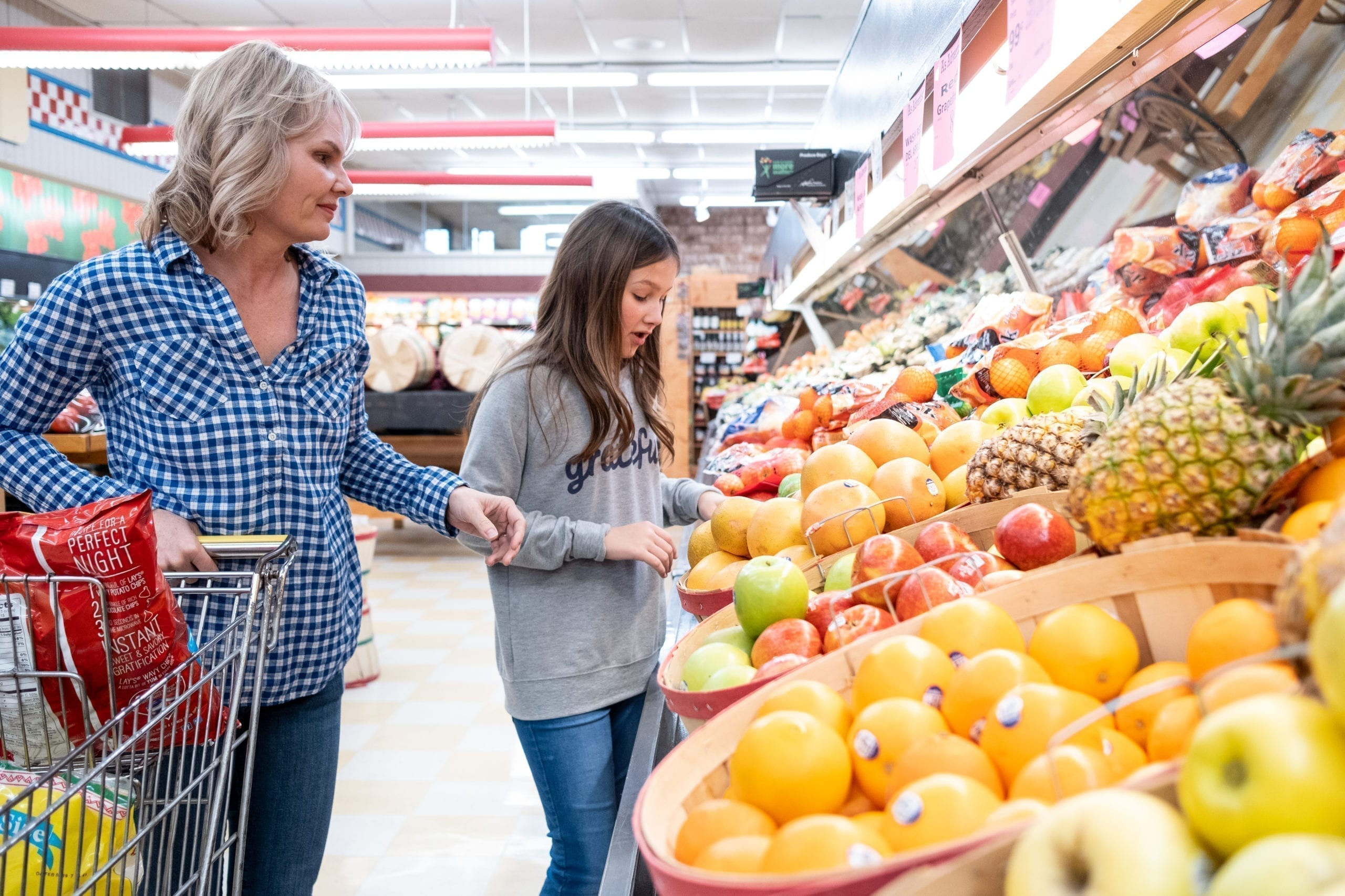 young girl at grocery store with mom looking at produce