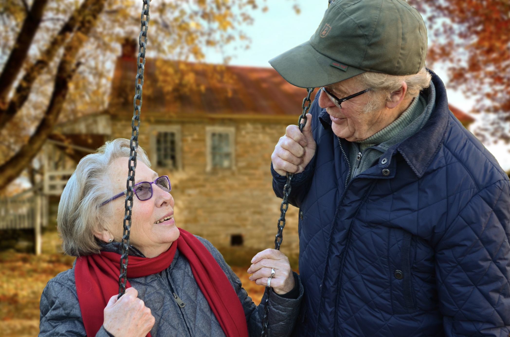 elderly couple looking at each other and smiling on a swing set