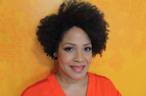 Ijeoma Oluo wearing orange shirt against a yellow background