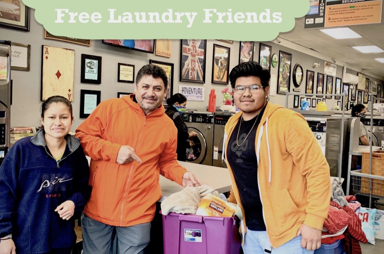 three people standing in a laundry mat