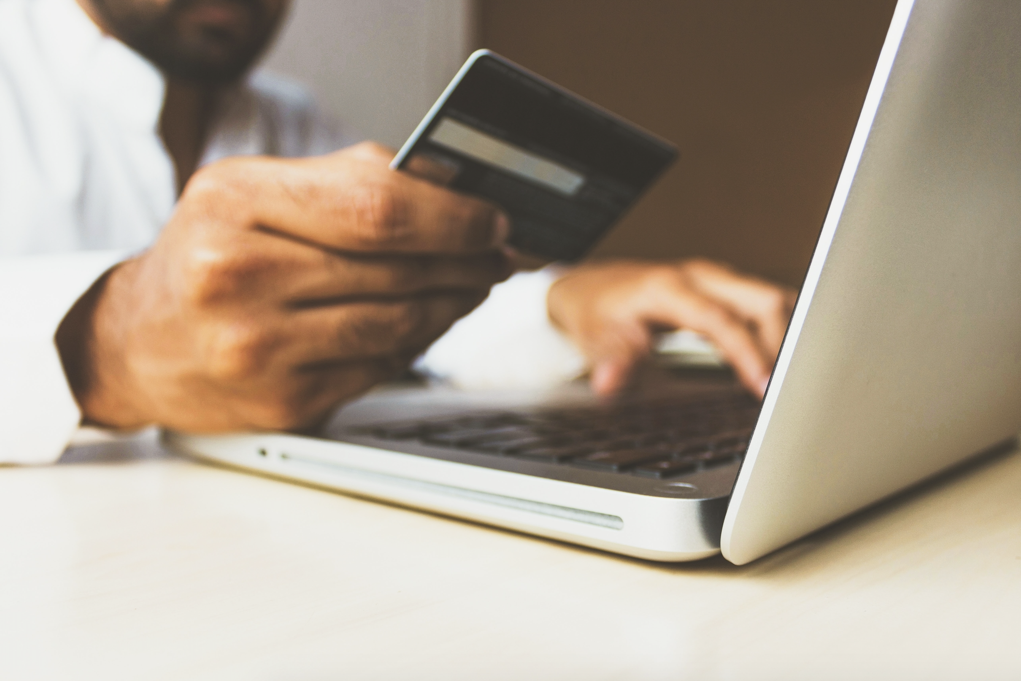 person sitting at laptop using their debit card to make a purchase