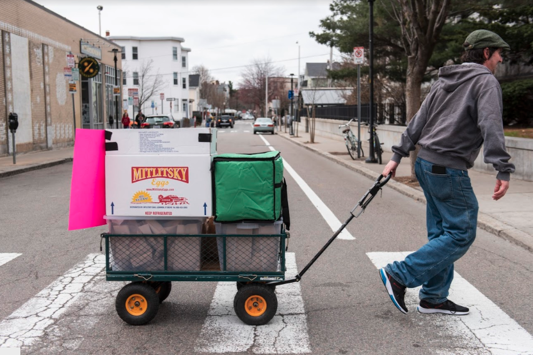 man pulling a wagon full of food across a street