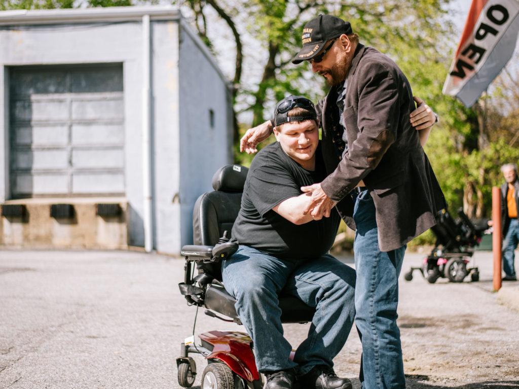 two veteran men hugging