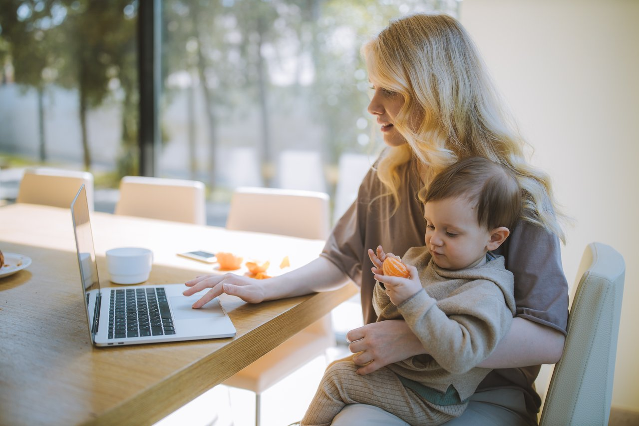 A mother sits at her computer with a toddler on her lap.