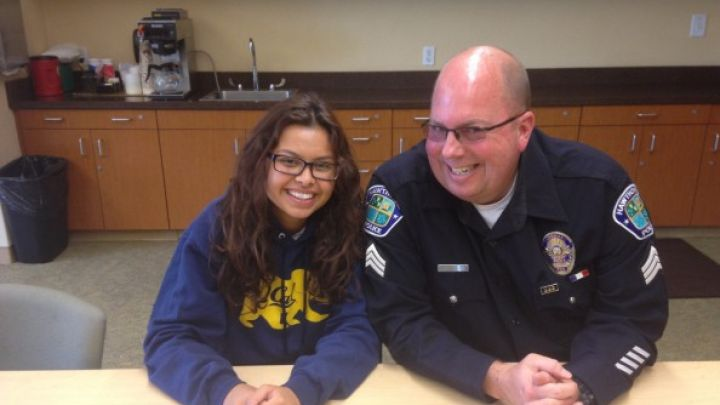 young girl sitting next to a police man smiling