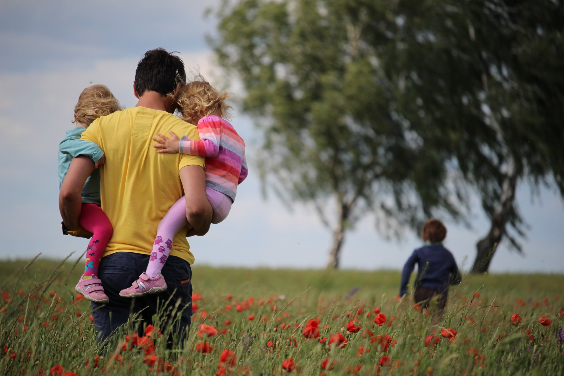 A man walking through a field of flowers holding two children