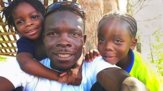 A Black father with his two children smiling at the camera