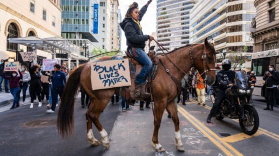 A Black woman on a horse with a sign that says