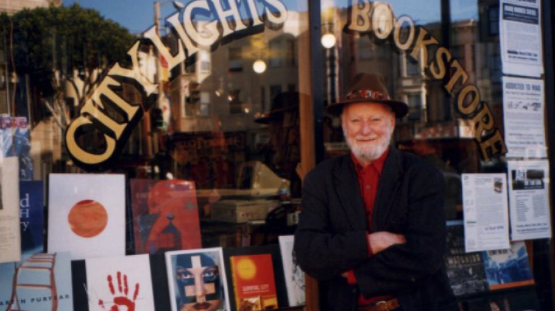 A man in hat standing in front of a bookstore